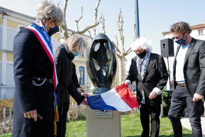 La maire deRomans-sur-Isère, Marie-Hélène Thoraval, et la famille de Julien Vinson, l'une des victimes, dévoilent une plaque commémorative et une sculpture de l'artiste R. Toros lors de la cérémonie en mémoire des victimes de l'attaque au couteau du 4avril2020.