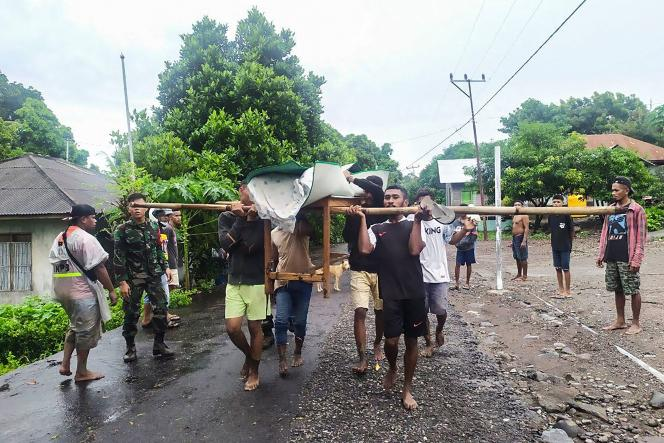 Pada tanggal 5 April mayat penduduk desa yang terkena dampak banjir dibawa pergi di Lombardy, Flores timur.