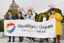 Activists gather in front of parliament before they submit a petition in Tokyo Thursday, March 25, 2021. LGBTQ and other human rights activists submitted a petition with over 106,000 signatures to Japan's ruling party Thursday, calling for an LGBT equality law to be enacted before the Tokyo Games, saying Japan as host nation should live up to the Olympic charter banning gender and sexual discrimination. (Kyodo News via AP)