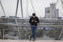 An Iranian man uses his smartphone while standing on a bridge that is equipped with a Huawei 5G modem in the Water and Fire park in northern Tehran on February 16, 2021. Iran's first 5G network has ran by the Irancell company which is an Iranian telecommunications company that operates Iran's largest 2G-3G-4G-4.5G also 5G mobile network, and fixed wireless TD-LTE internet services. (Photo by Morteza Nikoubazl/NurPhoto) (Photo by Morteza Nikoubazl / NurPhoto / NurPhoto via AFP)