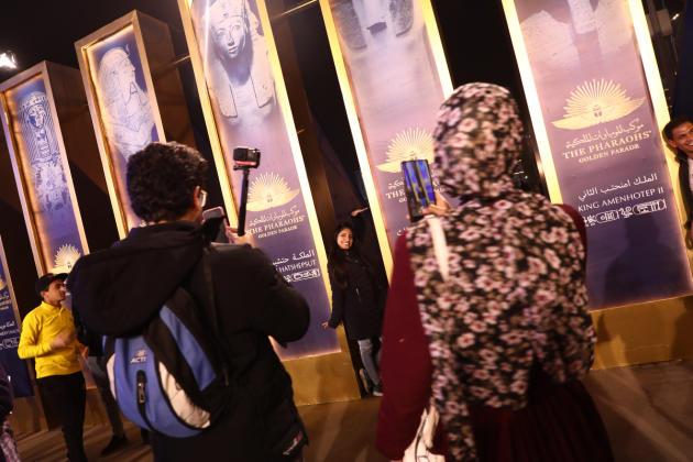 Les flaneurs s'immortalisent devant les posters de la cérémonie, au Caire, le 3 avril 2021.