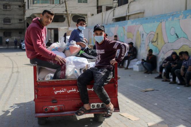Des jeunes palestiniens emportent des vivres qu'ils ont reçues d'un centre de distribution d'aide géré par les Nations Unies, à Gaza, le 7 avril.