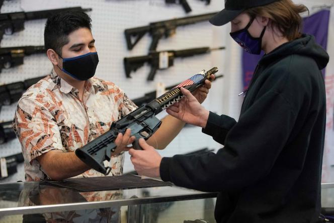 Un client prend en main un fusil semi-automatique dans un magasin d'armes à feu, à Orem (Utah), le 4 février 2021.