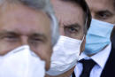 Brazilian President Jair Bolsonaro, center, arrives for a press conference following a meeting about the federal government's COVID-19 pandemic response at the presidential residence Alvorada Palace in Brasilia, Brazil, Wednesday, March 24, 2021. (AP Photo/Eraldo Peres)