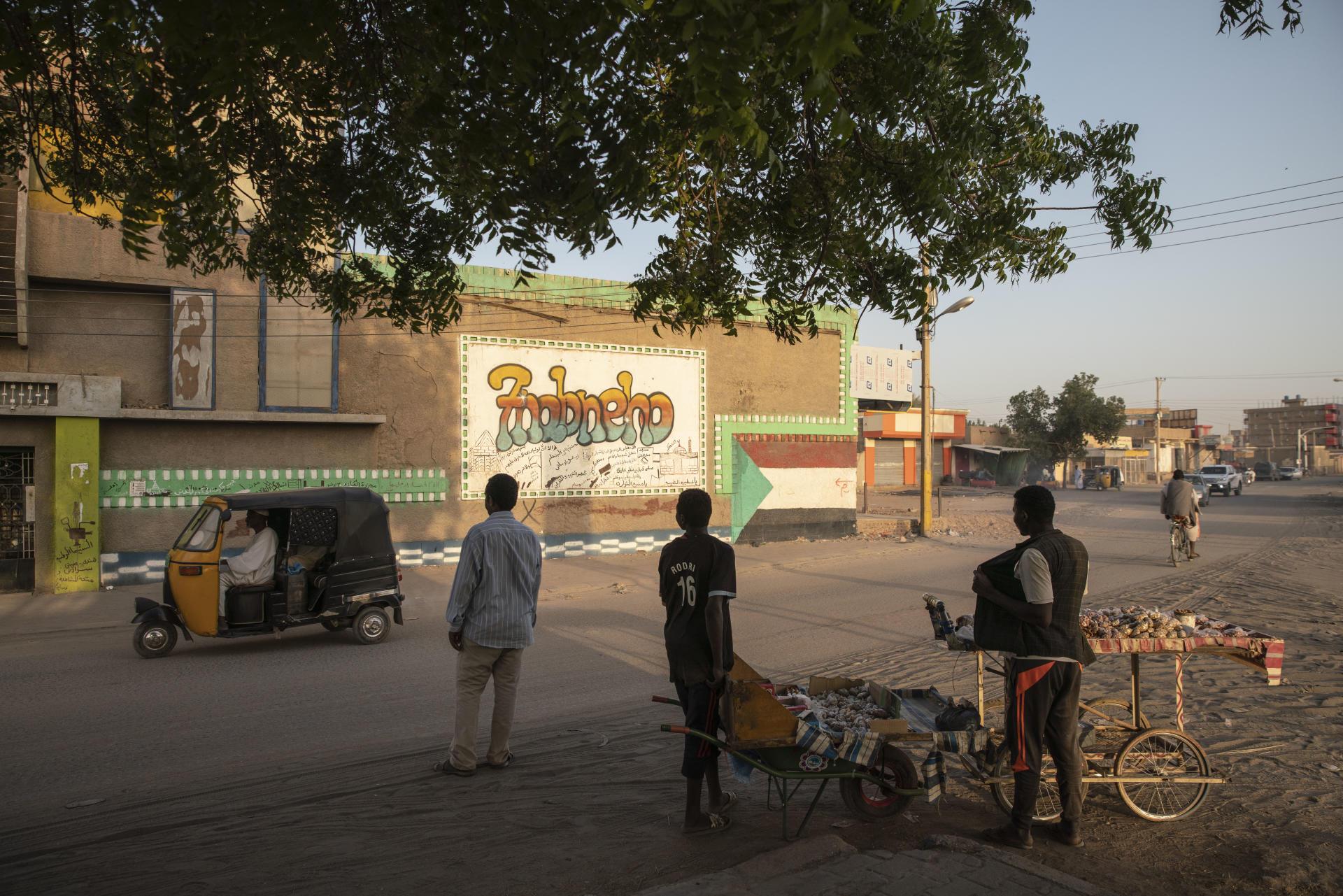Vendeurs ambulants devant un vieux cinéma d'Atbara. Au fil du temps, les salles ont fermé les unes après les autres, victimes de trente années de répression et de censure par le régime militaro-islamiste. Aujourd'hui, si la façade subsiste, le bâtiment a été reconverti en atelier de ferronnerie.