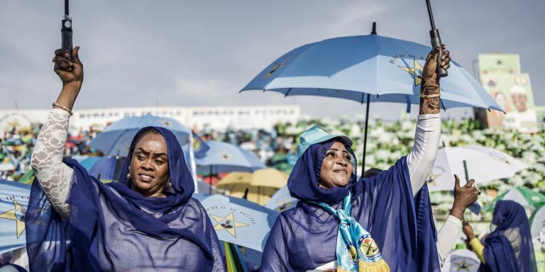 TOPSHOT - Supporters raise their umbrellas to cheer during the last election campaign rally for Chadian President Idriss Deby Itno in N'Djamena on April 9, 2021 ahead of the Presidential election. Chad's citizens are set to go to the polls for the first round of the Presidential election on April 11, 2021.  / AFP / MARCO LONGARI