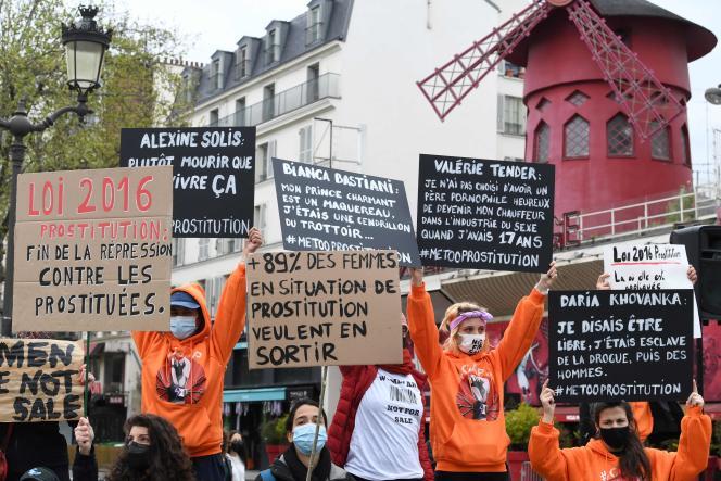 Des survivantes de la prostitution, dont certaines tiennent des pancartes, se rassemblent devant le cabaret leMoulin rouge pour demander l'application de la loi française de 2016 sur la prostitution, à Paris, dimanche 11avril 2021.
