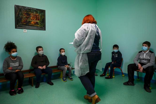 Une infimière explique aux écoliers comment effectuer leurs tests de dépistage du Covid-19, à Lavoncourt (Haute-Saône), le 1er mars.