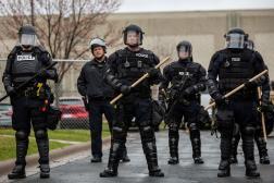 Des officiers de police se tendant devant la commissariat de Brooklyn Center, le 12 avril, au lendemain d'une nuit d'émeutes.