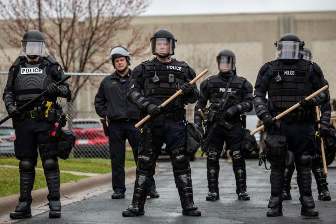 Des officiers de police se tiennent devant la commissariat de Brooklyn Center, le 12avril, au lendemain d'une nuit d'émeutes.