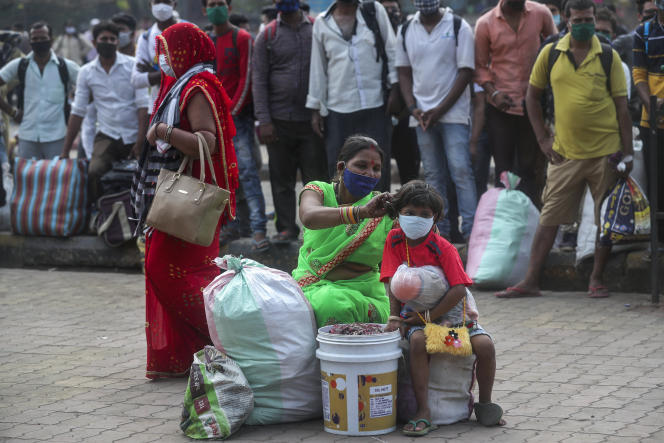 Une famille attend un train à la gare de Lokmanya Tilak à Bombay, le 11 avril. L'Inde met en place de nouveaux confinements locaux.