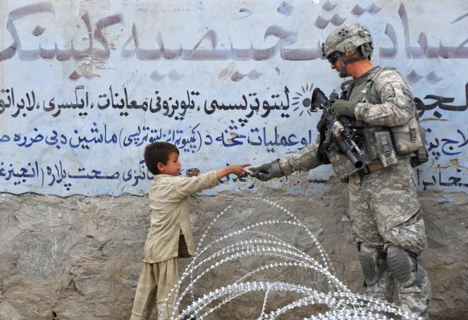 Un enfant offre un cadeau à un soldat américain à Khogyani, dans la province de Nangharar, en Afghanistan, le 20 février 2010. C'est la plus longue guerre dans laquelle les Etats-Unis se sont engagés.