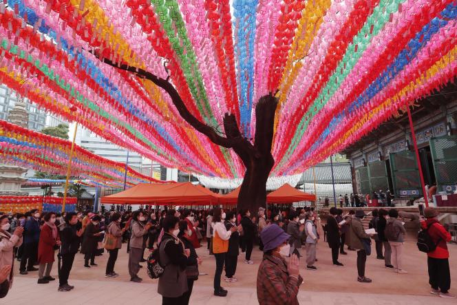 Des personnes prient pendant un service au temple bouddhiste Jogyesa à Séoul, en Corée du Sud, lundi 12 avril 2021. Le pays fait partie de ceux ayant opté pour une stratégie d'élimination du virus.