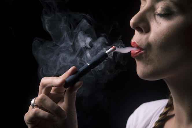 Une femme vapote une Heets, une mini-cigarette IQOS, un dispositif qui exploite la technologie du«heat not burn» : le tabac est chauffé sans aller jusqu'à la combustion.A Clichy, en septembre 2017.