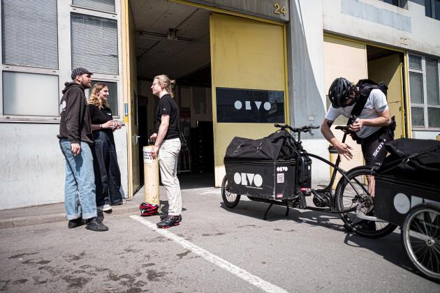 Un livreur ajuste son vélo à côté d'employés en pause, à Paris, le 19 avril.