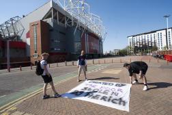 Des supporteurs de Manchester United déploient une banderole hostile au projet de Superligue à l'extérieur du stade d'Old Trafford.