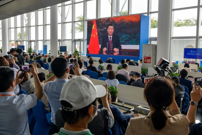 Des journalistes regardent un écran montrant le président chinois, Xi Jinping, prononçant un discours lors de l'ouverture de la conférence annuelle 2021 du Boao Forum for Asia, à Boao (Hainan), dans le sud de la Chine, le 20 avril 2021.