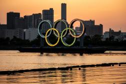 The Olympic rings are lit at the waterfront of Odaiba in Tokyo on April 20, 2021. / AFP / Philip FONG