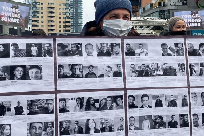 Un homme tient des photos de personnes qui seraient détenues par la police en Biélorussie, lors d'une manifestation, à Toronto, au Canada, le 3 avril.