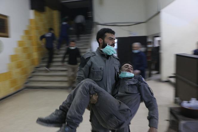 Un homme syrien, membre de la défense civile, transporte un homme touché par un gaz chimique à l'hôpital de campagne, après l'attaque présumée au chlore dans la Ghouta orientale à Damas, le 6 mars 2018.