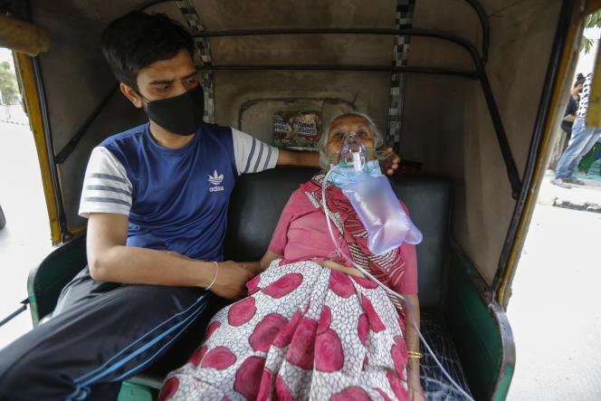 Une femme atteinte du Covid-19 attend à l'intérieur d'un pousse-pousse d'être admise dans un hôpital pour être soignée, à Ahmedabad (Inde), le 17 avril.