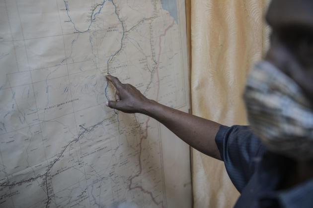 Amine Ali Al-Hassan, représentant du conseil exécutif du syndicat national, pointe du doigt une vieille carte du Soudan où sont encore visibles les lignes de chemin de fer aujourd'hui détruites ou inutilisées, en avril 2021.