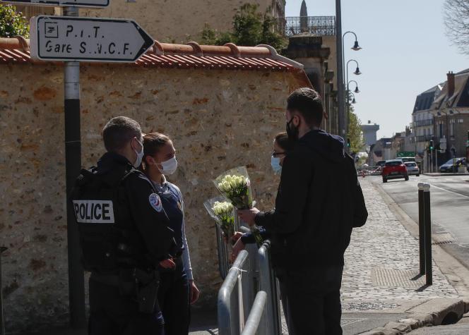 Des passants apportent des fleurs en hommage à Stéphanie M., tuée à l'entrée du commissariat de police, à Rambouillet, le 24 avril.