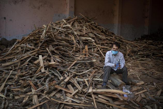 Un homme attend l'incinération de membres de sa famille morts du Covid-19, assis sur un tas de bois servant à alimenter les crémations à New Delhi, le 24 avril. La consommation de bois pour incinérer les corps est telle que les autorités commencent à couper les arbres des parcs de la ville.