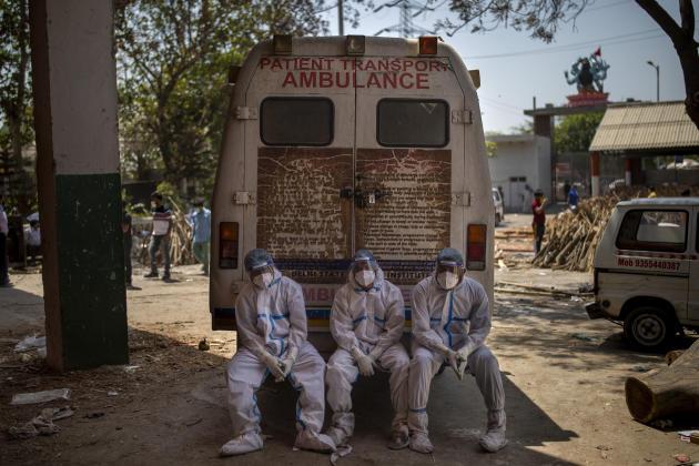 Des travailleurs se reposent après avoir convoyé les corps de victimes du Covid-19 sur un site de crémation à New Delhi, le 24 avril.