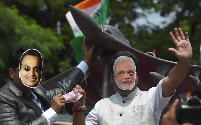 Des manifestants portent des masques du premier ministre indien Modi (droite) et d'Anil Ambani, devant la réplique d'unRafale, à Bombay, en 2018.