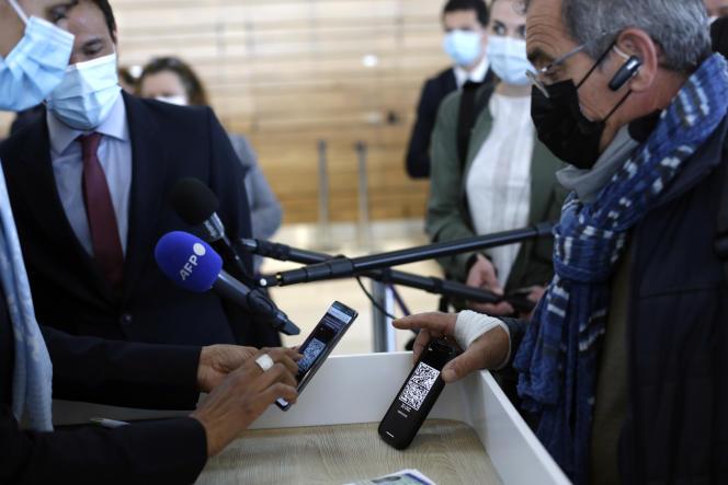 Un passager montre son téléphone portable avec un test d'antigène et de PCR téléchargé avant d'embarquer à l'aéroport de Paris-Orly, mardi 27 avril 2021.
