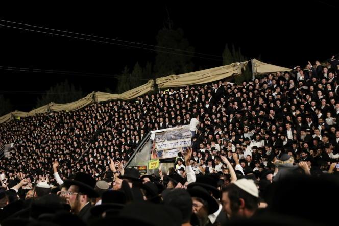 Des fidèles juifs chantent et dansent alors qu'ils se tiennent sur des tribunes lors de l'événement Lag Baomer au mont Méron, dans le nord d'Israël, le 29 avril 2021.