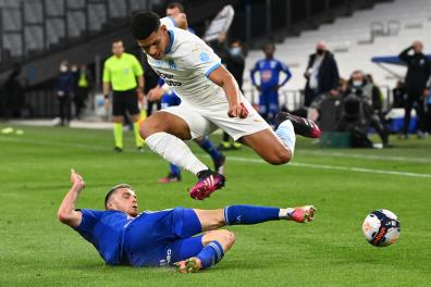 Marseille's Brazilian forward Luis Henrique (up) fights for the ball with Strasbourg's French defender Frederic Guilbert during the French L1 football match between Marseille and Strasbourg at the Velodrome stadium in Marseille on April 30, 2021. / AFP / Christophe SIMON