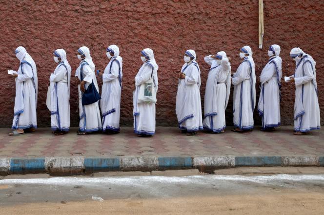 Katholieke zusters komen in de rij om te stemmen, met maskers op, in Calcutta op 29 april.