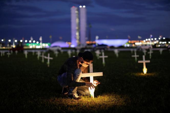 Un homme allume une bougie à côté d'une croix symbolisant les morts du coronavirus, devant le Congrès, à Brasilia, le 27 avril 2021.