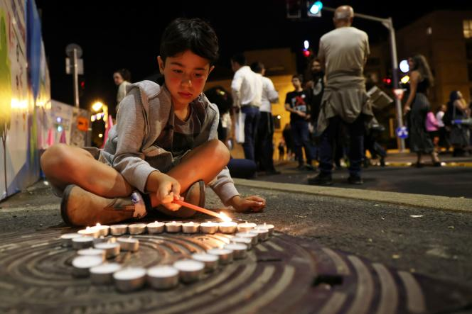 Un garçon allume des bougies pendant une veillée pour les personnes tuées et blessées dans la bousculade du mont Meron en Israël, à Jérusalem, le 1er mai 2021.