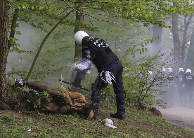 Un policier interpelle un homme dans le parc du bois de la Cambre, à Bruxelles, en Belgique, le 1er mai.