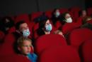 (FILES) In this file photo taken on March 14, 2021 people watch a movie in a cinema theatre, in Nantes, as part of a nationwide action to reopen movie theatres closed since the beginning of the covid-19 pandemic. French President Emmanuel Macron announced on April 29, 2021 that cafes, restaurants, cinemas and museums will reopen partially on May 19, 2021 after seven months amidst the coronavirus pandemic. / AFP / LOIC VENANCE