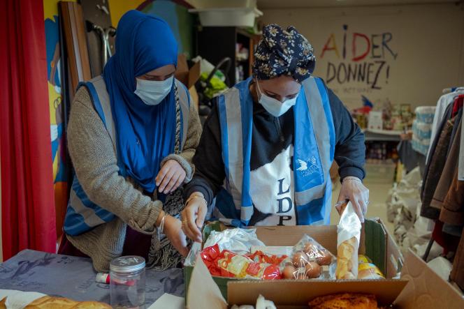 Nassera et Nouria, volontaires au Secours populaire d'Aubervilliers, vérifient le contenu d'un carton de nourriture qui sera donné à une famille, le 30 avril.