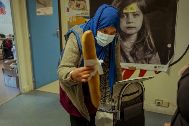 Nassera, volontaire et trésorière au Secours populaire d'Aubervilliers, ajoute une baguette lors de la distribution de nourriture, le 30 avril 2021.