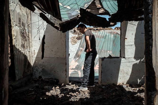 مردی در ویرانه تجارت سوخته خود در ماكسات ، قرقیزستان ، در مرز با تاجیكستان ، 2 مه 2021.