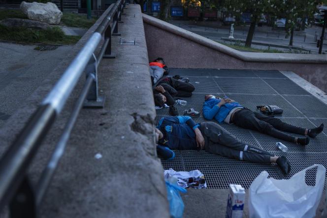Installés sur une bouche d'aération, dans les jardins du Trocadéro, des mineurs isolés dorment à même le sol, à Paris, le 27 avril.