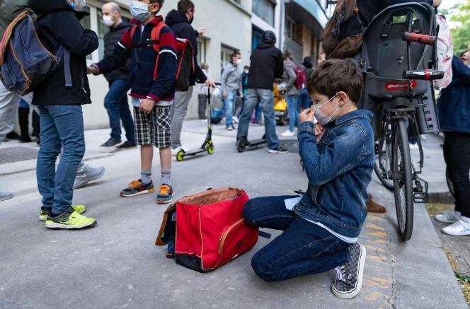 Un garçon ajuste son masque avant d'entrer dans son école primaire, à Paris, le 26 avril 2021.