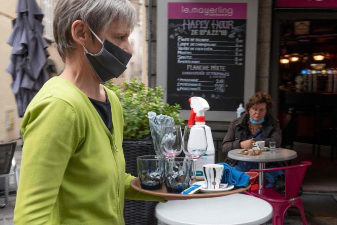 Un serveur passe devant un client assis à une terrasse, Place Saint-Dominique, à Clermont-Ferrand, le 22octobre 2020.