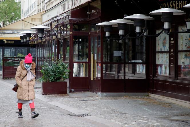 Une femme passe devant des restaurants fermés en raison des restrictions sanitaires, àParis, le 6 mai.