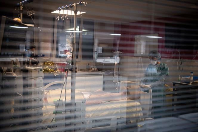 Un membre du personnel médical auprès d'une patiente dans une unité de soins intensifs pour les personnes infectées par le Covid-19, à l'hôpital AP-HP Louis Mourier de Colombes, le 4 mai 2021.