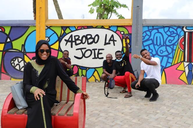 Des membres de l'association Les Enfants d'Abobo posent devant une fresque du peintre Obou, le 4mai 2021.