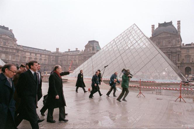 Le président François Mitterrand (3e à gauche), accompagné du ministre de la culture François Léotard (2e à gauche) et de l'architecte américain Ieoh Ming Pei (à gauche), visite, le 4 mars 1988, la Pyramide du Louvre à Paris.
