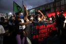 People hold a banner as they protest against police violence outside Jacarezinho slum, after a police operation which resulted in 25 deaths, in Rio de Janeiro, Brazil, May 7, 2021. REUTERS/Ricardo Moraes
