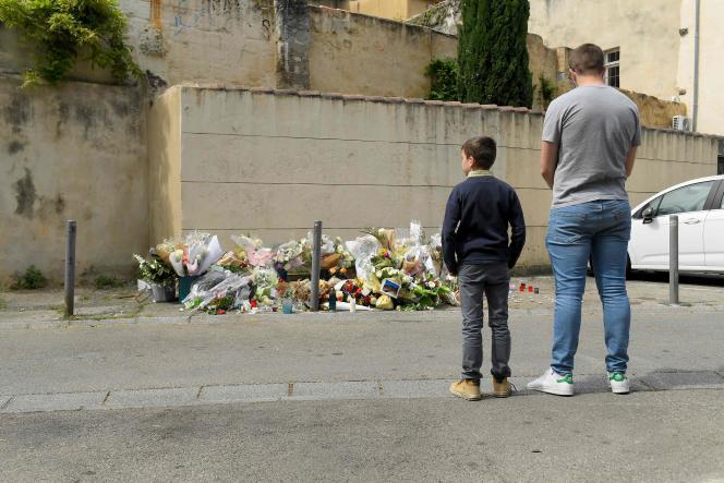 Un homme et son fils se recueillent sur le lieu du meurtre du brigadier Eric Masson, dimanche 9 mai 2021, à Avignon.